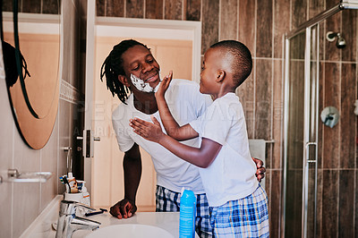 Buy stock photo Cropped shot of a little boy helping his father to shave his beard