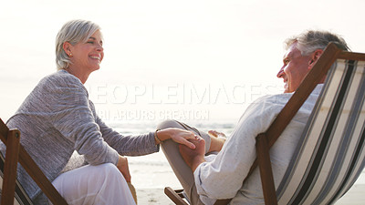 Buy stock photo Cropped shot of an affectionate senior couple relaxing on loungers at the beach on a summer's day