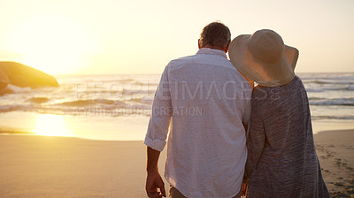 Buy stock photo Rearview shot of an unrecognizable senior couple walking towards the beach at sunset