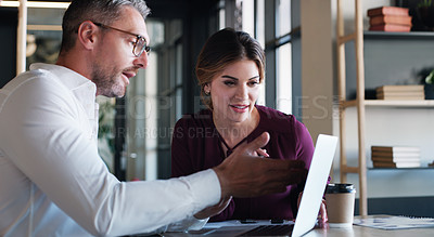 Buy stock photo Shot of a businessman and businesswoman using a laptop and having a discussion in a modern office
