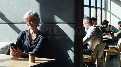 Buy stock photo Shot of a mature businesswoman using a smartphone in a modern office