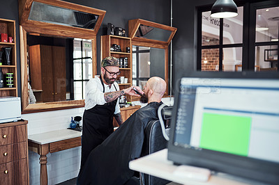 Buy stock photo Cropped shot of a handsome young barber trimming and lining up a clients beard inside his barbershop