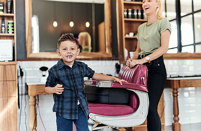 Buy stock photo Cropped shot of an adorable little boy eating a lollipop after getting a fresh haircut at a salon