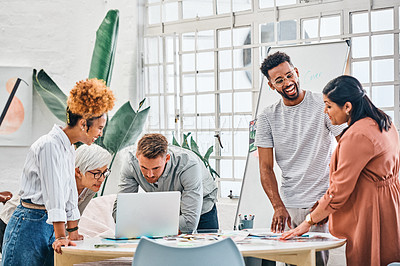 Buy stock photo Cropped shot of a diverse group of businesspeople standing together and brainstorming over paperwork and technology in the office