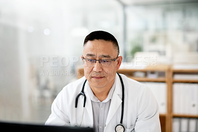Buy stock photo Cropped shot of a mature doctor working on a computer inside his office at the hospital