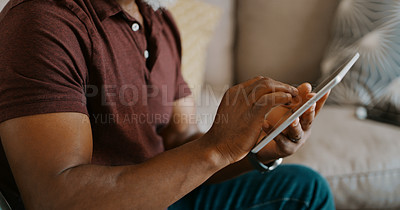 Buy stock photo Cropped shot of an unrecognizable man sitting alone on his sofa and using a tablet
