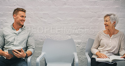 Buy stock photo Shot of a businessman and businesswoman chatting in the waiting room of a modern office
