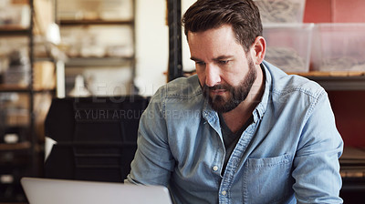 Buy stock photo Shot of a young businessman using a laptop in a creative office