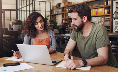 Buy stock photo Shot of a young businessman and businesswoman using a laptop while designing a blueprint in a creative office