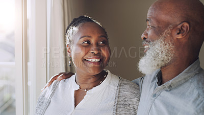 Buy stock photo Cropped shot of a happy senior couple standing and holding each other affectionately while looking out of their window