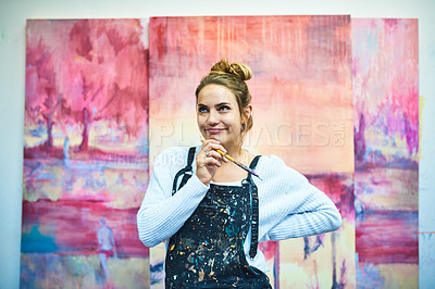 Buy stock photo Cropped shot of an attractive young female painter looking thoughtful while standing in her art studio