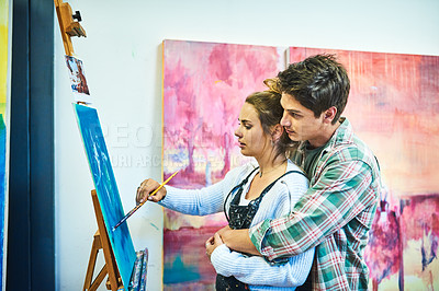 Buy stock photo Cropped shot of an affectionate young man embracing his girlfriend from behind while she's painting on a canvas in an art studio