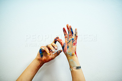 Buy stock photo Cropped shot of an unrecognizable female painter's paint-covered hands against a grey background