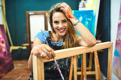 Buy stock photo Cropped portrait of an attractive young female painter smiling while sitting in her art studio