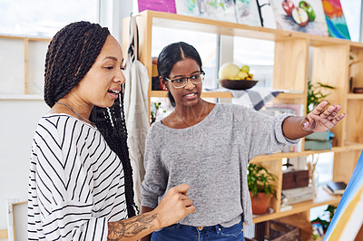 Buy stock photo Cropped shot of two young women discussing something on a canvas in a art studio