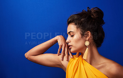 Buy stock photo Shot of a beautiful young woman posing against a blue background