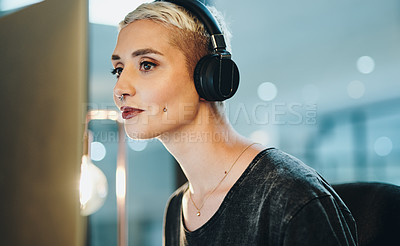 Buy stock photo Cropped shot of an attractive young businesswoman listening to music while working on her computer in the office