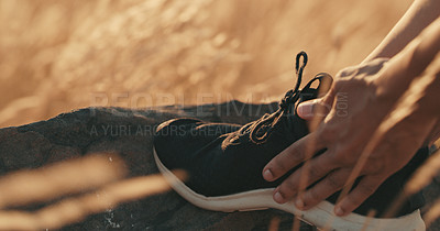 Buy stock photo Closeup shot of an unrecognisable woman tying her shoelaces outdoors