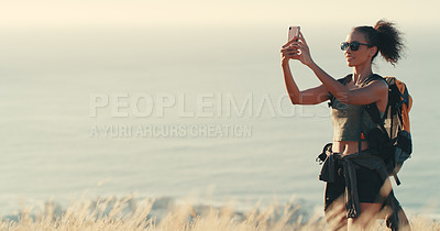 Buy stock photo Shot of a young woman taking photos while out on a hike