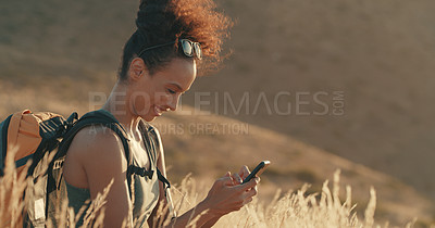 Buy stock photo Shot of a young woman using a cellphone while out on a hike