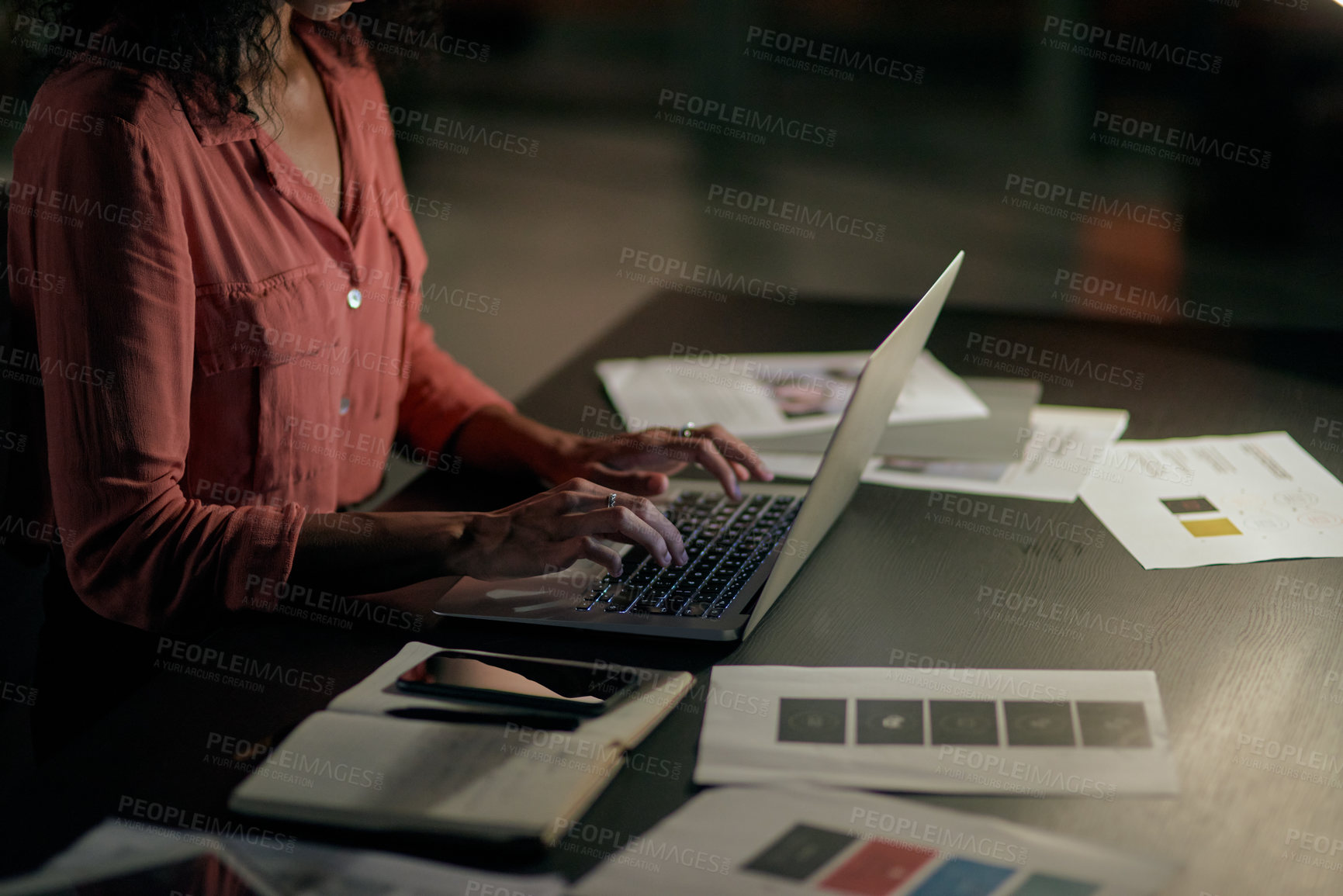 Buy stock photo Cropped shot of an unrecognizable businesswoman sitting alone and using her laptop during a late night in the office