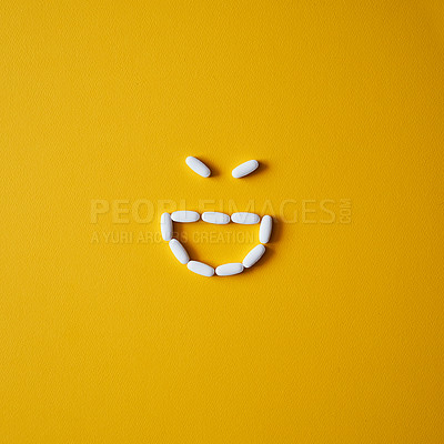 Buy stock photo Studio shot of tablets arranged in the shape of a smiley face against a mustard background
