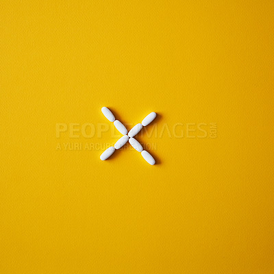 Buy stock photo Studio shot of tablets arranged in the shape of a multiplication against a mustard background