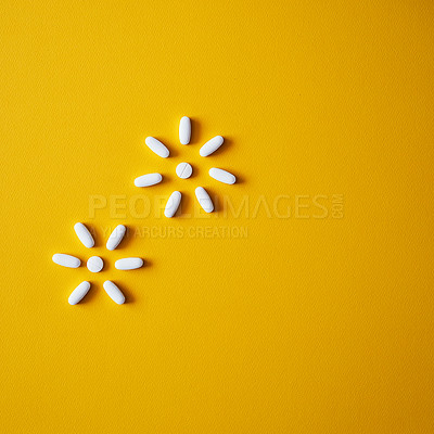 Buy stock photo Studio shot of tablets arranged in the shape of snowflakes against a mustard background