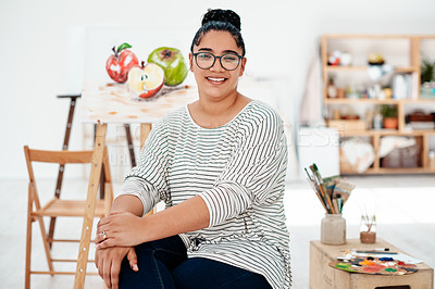 Buy stock photo Cropped portrait of an attractive young artist sitting next to her painting during an art class in the studio
