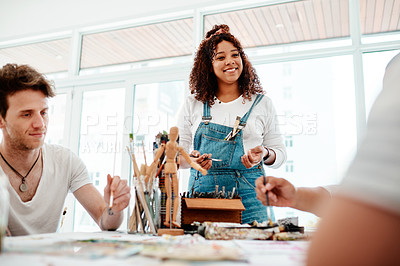 Buy stock photo Cropped shot of an attractive young artist standing and talking to her friends during an art session in the studio