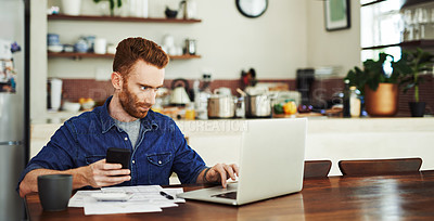 Buy stock photo Shot of a young man using a cellphone and laptop while going through paperwork at home