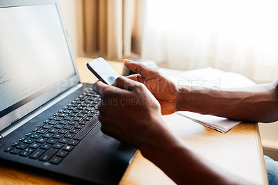 Buy stock photo Cropped shot of an unrecognizable man texting on his cellphone while working on his laptop at home during the day