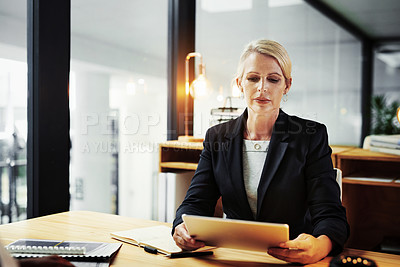Buy stock photo Shot of a mature businesswoman using a digital tablet during a late night in a modern office