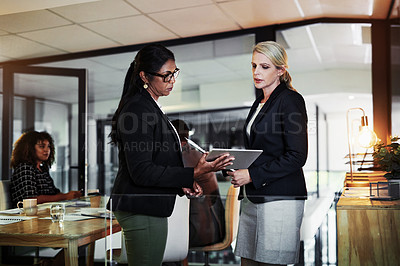 Buy stock photo Shot of two businesswomen using a digital tablet during a late night discussion in a modern office