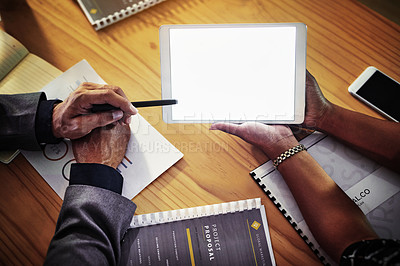 Buy stock photo Cropped shot of a businessman and businesswoman using a digital tablet during a late night meeting in a modern office