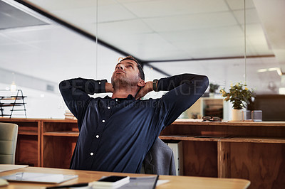 Buy stock photo Shot of a mature businessman reclining in his chair during a late night in a modern office