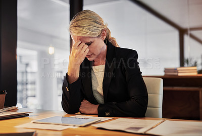 Buy stock photo Shot of a mature businesswoman looking stressed during a late night in a modern office