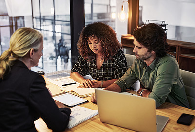 Buy stock photo Shot of a group of businesspeople using a digital tablet during a late night meeting in a modern office