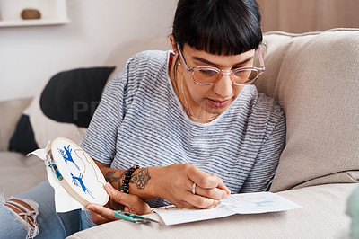 Buy stock photo Shot of a beautiful young woman doing embroidery at home