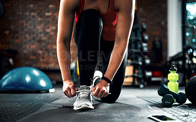 Buy stock photo Cropped shot of an unrecognizable young female athlete tying her laces while working out in the gym