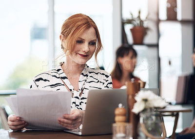 Buy stock photo Cropped shot of an attractive middle aged woman doing paperwork while being seated inside of a coffee shop during the day
