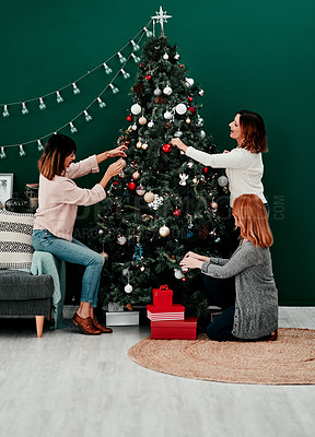 Buy stock photo Shot of three attractive middle aged women decorating a Christmas tree together at home