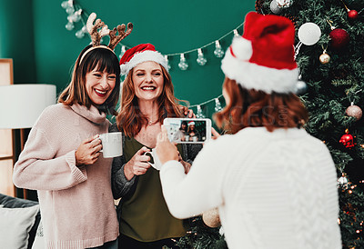 Buy stock photo Cropped shot of of a cheerful middle aged woman taking a picture of her two friends at home during Christmas time
