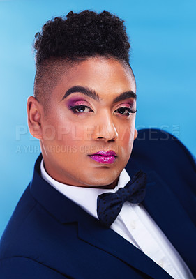 Buy stock photo Portrait of a gender fluid young businessman posing against a blue background