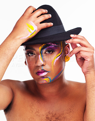 Buy stock photo Portrait of a gender fluid young man wearing face paint and a hat posing against a white background
