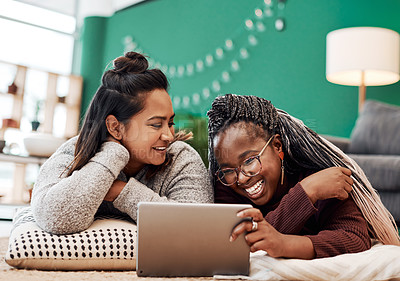 Buy stock photo Shot of two young women using a digital tablet together on the floor at home