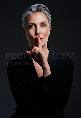 Buy stock photo Studio portrait of a beautiful mature woman posing with her finger on her lips against a dark background