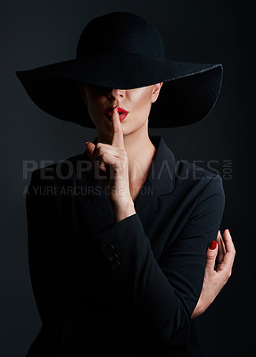Buy stock photo Studio shot of a beautiful mature woman wearing a hat and posing with her finger on her lips against a dark background