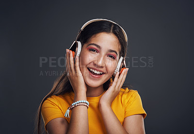 Buy stock photo Cropped portrait of an attractive teenage girl standing against a dark background alone and listening to music through headphones