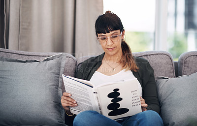 Buy stock photo Cropped shot of an attractive young woman sitting alone in her living room and reading a book